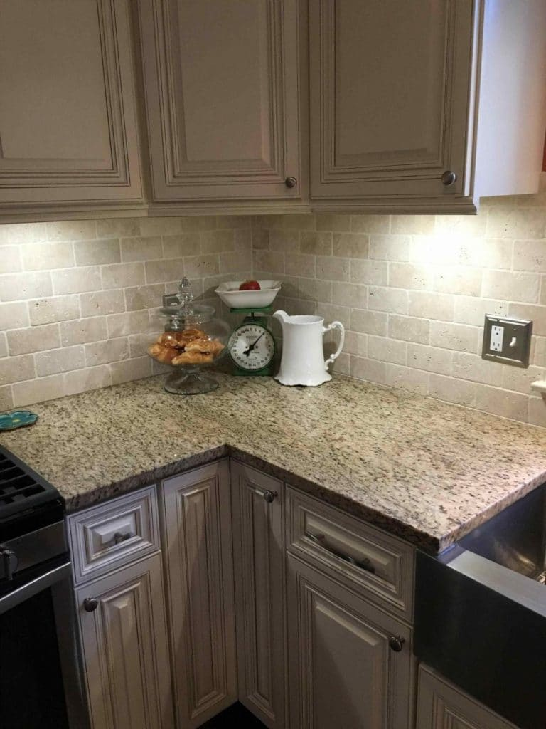 taupe-kitchen-cabinets-off-white-brick-backsplash-corner